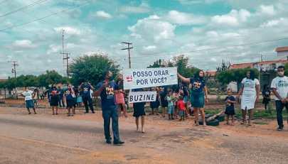 """Semáforo de Oração: Os jovens adventistas foram para as ruas oferecer orações pelas famílias. Faixas com frases como """"Posso orar por você"""" e """"Buzine"""" eram usadas para parar os motoristas e orar com eles. ( Foto: Reprodução)"""