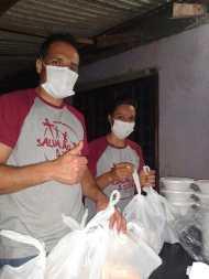 Voluntários durante preparação de refeições. [Foto: Reprodução].