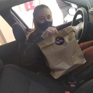 Clientes receberam alimentos no formato drive-thru. [Foto: Reprodução].