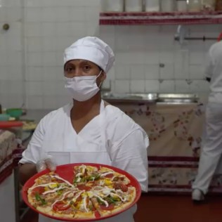 Cozinheiras do abrigo preparam as pizzas que foram ofertadas. (Foto: Colaboração)