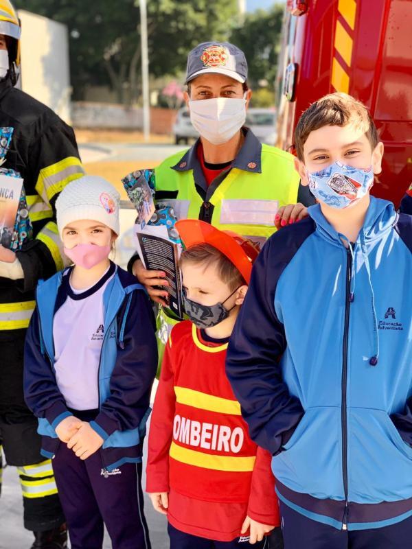 Algumas crianças de caracterizaram de bombeiros para homenagear os profissionais da área. Crianças se divertem ao conhecerem funcionalidades das viaturas dos bombeiros. [Foto: Reprodução].