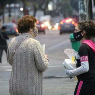 Aluna oferece kit de café da manhã e conversa com pessoa que passava pela praça. [Foto: Paulo Ribeiro].