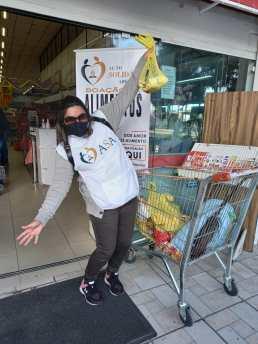 Voluntária posa para foto durante arrecadação de alimentos em supermercado. [Foto: Reprodução].