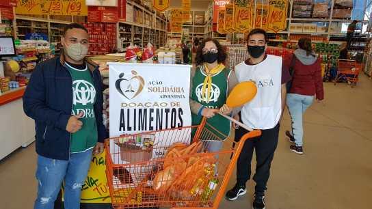Integrantes do projeto +Vida durante arrecadação de alimentos em supermercado. [Foto: Reprodução].