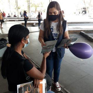 Voluntária entregando revista. (Foto: reprodução)