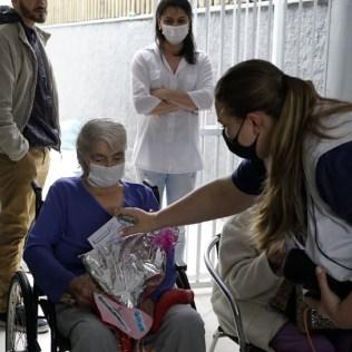 Professora Juliana entrega presentes para idosa. Crianças posam para foto após homenagearem idosos. [Foto: Paulo Ribeiro].