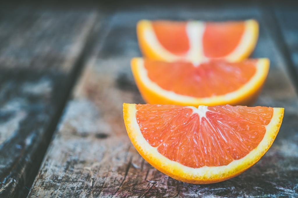 laranjas cortadas em cima de madeira para fazer óleo de laranja