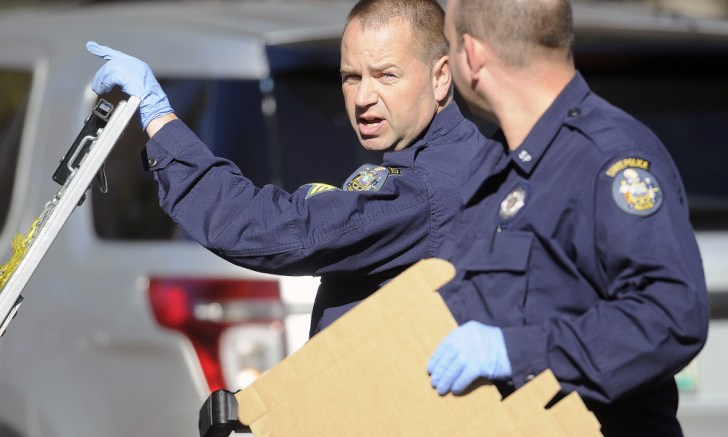 State police Detective Sgt. Scott Bryant, left, confers Tuesday with Detective Larry Rose while collecting evidence at the Balcer residence in Winthrop, where 17-year-old Andrew Balcer is accused of killing his parents Antonio and Alice Balcer.