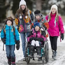 Group of children walking and rolling to school in the winter.