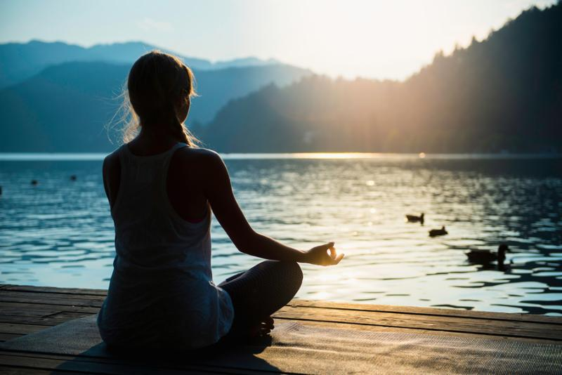 Young woman meditating by the lake sunset water birds
