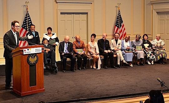 NEA Heritage Fellows sit in a row in the back of a stage while a man at the podium gestures towrds them with his hand.