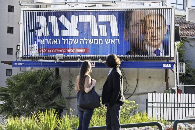 Sur un panneau publicitaire tournant de Tel Aviv, le visage du premier ministre Benyamin Netanyahou fait place à celui de son opposant Yitzhak Herzog.