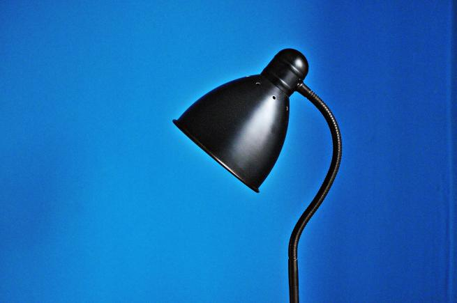 black lamp against blue wall