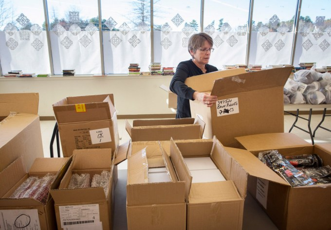 Cathy Houlihan of Cape Elizabeth packages toys at the Falmouth location of the Press Herald Toy Fund.
