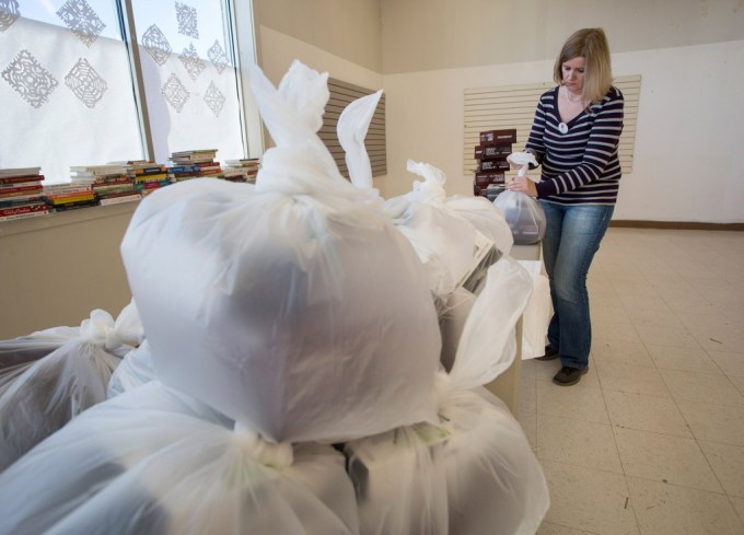 Diane McCabe of South Portland, who has volunteered with the toy fund for 29 years, ties up bags of toys.