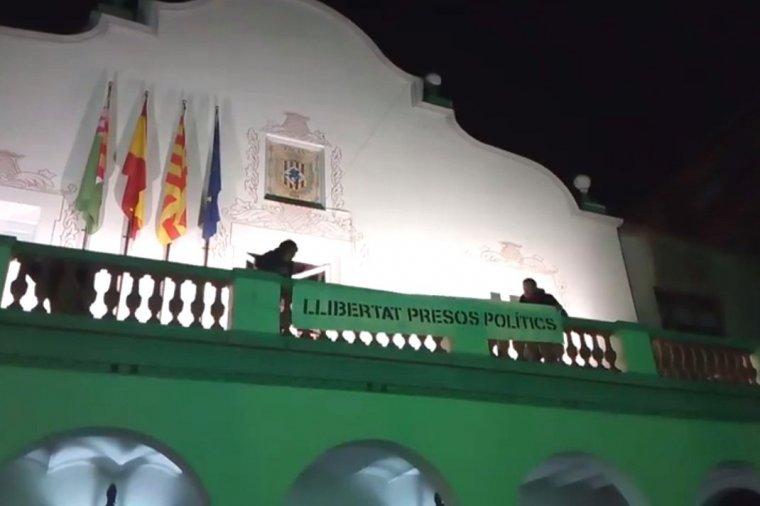 La pancarta en el moment de ser penjada al balcó de l'ajuntament