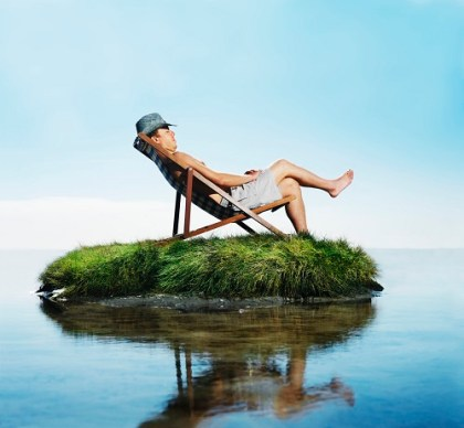 Man sleeping in deckchair on grass island, side view