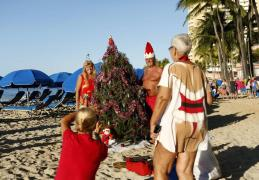 Staci Kennedy of Cape Cod, Massachusetts, takes a photo of her friends Pam Walker and Andy Hryniewich after they decorated a Christmas tree on the beach at Waikiki in Honolulu, Hawaii December 25, 2013. Kennedy and her friends have been taking part in this Christmas day festivity for 16 years. REUTERS/Kevin Lamarque (UNITED STATES - Tags: RELIGION SOCIETY)