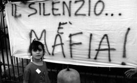 """Palermo , September 1993 - Demo against the killing of Father Puglisi - A female child in front of a banner with the writing """" Silence is Mafia """" Palermo , settembre 1993 - Protesta contro la mafia per l'uccisione di Padre Pugliesi - Una bambina di fronte ad uno striscione con la scritta """" Il silenzio è mafia """" *** Local Caption *** 00127716"""
