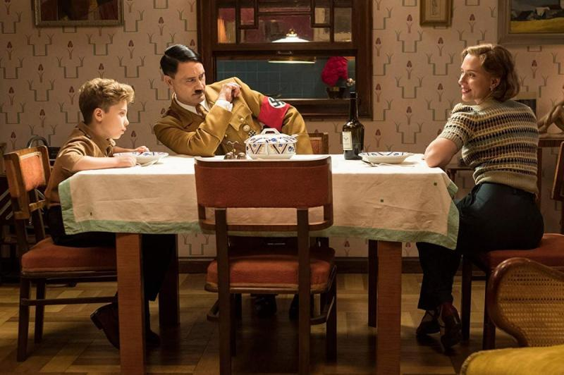 "Jojo (Roman Griffin Davis), ""Hitler"" (Taika Waititi) and Rosie (Scarlett Johansson) have a meal in Jojo Rabbit"