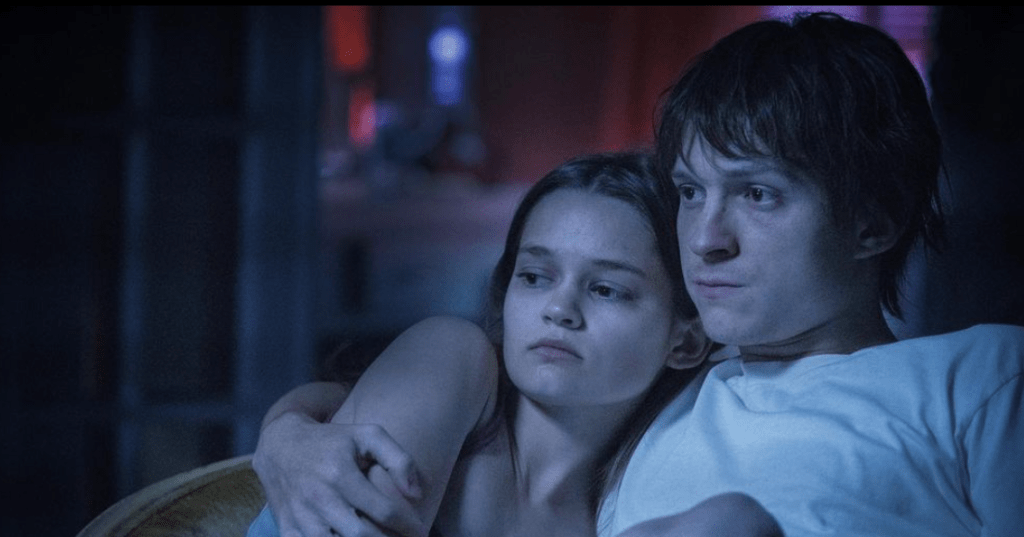 Image Description: a man and woman, both in their early 20s, are positioned on the right side of the screen, cuddling up. The camera only shows them from chest up and they are both staring off at the distance. The woman has long brown hair and is wearing a white vest top. The man has brown hair and is wearing a white shirt.
