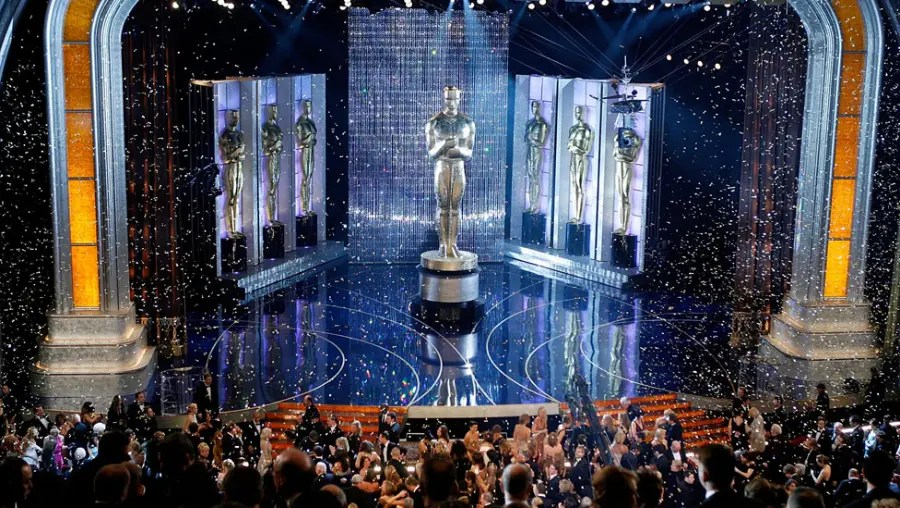 In the foreground are audience members sat in theatre seats, wearing glamorous tuxedos and dresses. Ahead of the audience in a stage lit in silver and blue, with a giant Oscar award statue erected in the centre of the stage.