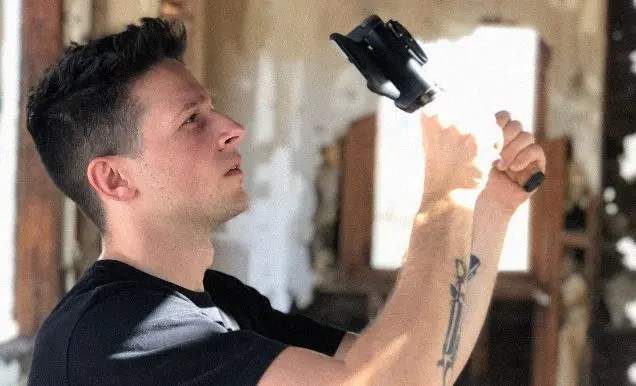 A man in a black t-shirt holds up an iPhone, attached to a small handheld rig, towards the ceiling of a rundown shack.