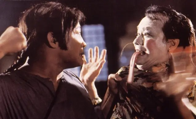 A man in a simple brown garment grabs another man by the collar and threatens to punch him. The man being held wears white makeup to look like a demon and has a fake, long devil tongue sticking out of his mouth.