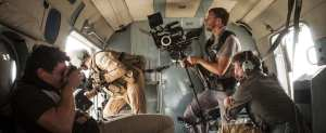 A picture of a camera film crew working in an airplane, filming.