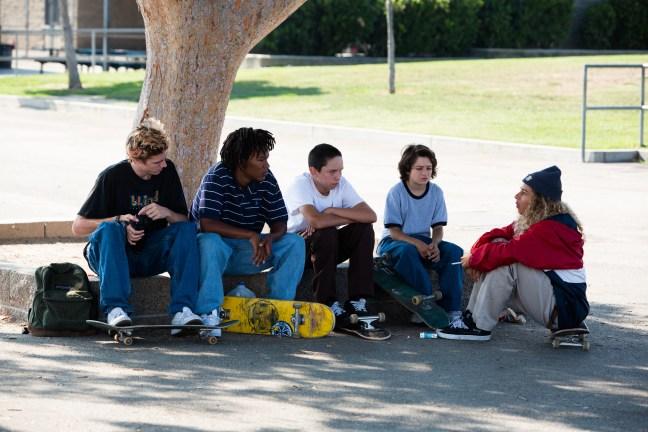 Parta kamarádů sedí u skateparku ve filmu Devadesátky