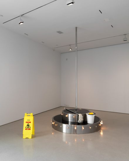 Elmgreen & Dragset, Go Go Go!, 2005, Brushed stainless steel platform, acrylic glass, polished stainless steel pole, light bulbs, light controls, mop, bucket with dirty water, foor sign Platform: 50 x 170 x 120 cm, pole length variable due to installation (max. 6 m) (photography by Steven Probert; Courtesy the artists and FLAG Art Foundation)