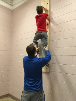 Gray assists a student who is CRUSHING the peg wall by almost making it the top! (Photo/Jaryd Leady)