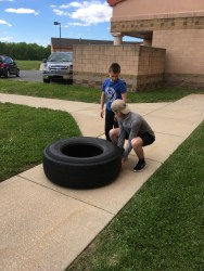 Hickman shows the proper form to a student before he takes his turn on the tire flip. Making sure to point out the squat position and the straight back. (Photo/Jaryd Leady)