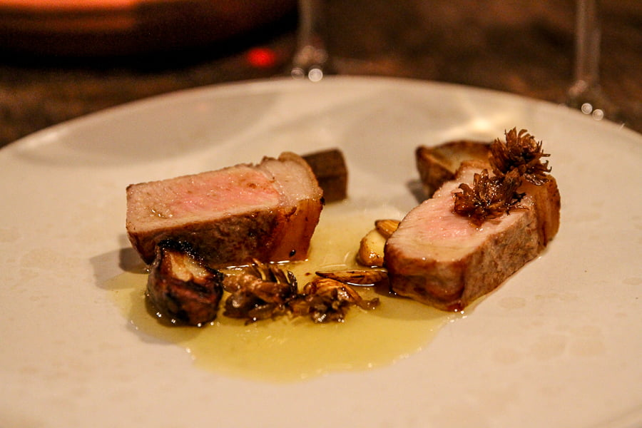 Pig with plum and black garlic on a sauce of butter.