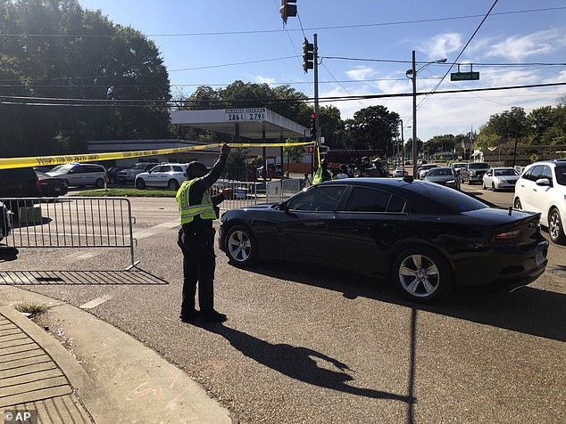 'The Postal Service is saddened at the event that took place today in Memphis,' USPS said in a statement. Pictured is a police officer allowing a police vehicle to pass under yellow crime scene tape in front of the Orange Mound post office