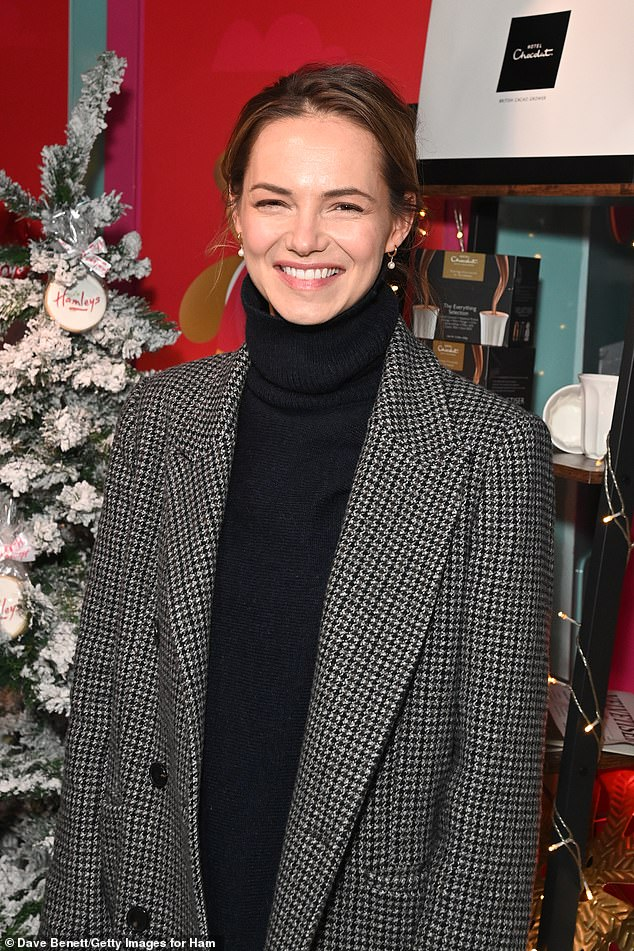 Festive spirit:Kara went lower-key, in a black turtle neck over flared jeans and a checked black and white trench