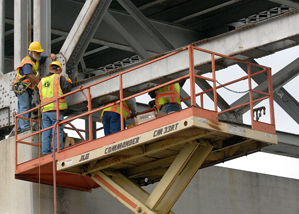 This year, the Minnesota Transportation Alliance will focus on the benefits of infrastructure investment. In this photo, a Minnesota Department of Transportation maintenance crew examines a corroded gusset plate June 8 on the Highway 43 bridge in Winona, Minn. (AP file photo)