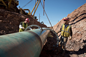 Workers remove a large clamp from a section of pipe during construction March 11 of part of the Keystone XL Pipeline Project. (Bloomberg file photo: Daniel Acker)