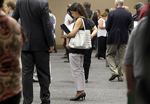 A woman waits to talk with employers at a July 15 job fair for laid-off IBM workers in South Burlington, Vt. (AP file photo)