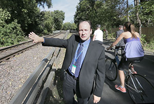 Southwest LRT deputy director Craig Lamothe gestures toward freight rail tracks in the Kenilworth Corridor during a tour Tuesday. Under a plan recommended by key local officials Wednesday, light rail vehicles would travel through the corridor in shallow tunnels. (Staff photo: Bill Klotz)