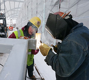Ironworker Sean Casey, left, assists Ron Rathbaum, right, as he welds a clip onto a bus shelter at Target Field Station. Both work for Bald Eagle Erectors, a company that has worked with the Metropolitan Economic Development Association. (Staff photo: Bill Klotz)