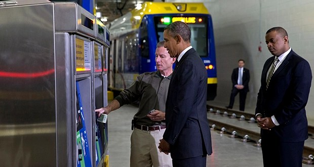 President Barack Obama and Transportation Secretary Anthony Foxx, right, listen as Metro Transit's Mark Fuhrmann shows them a ticket vending machine during a tour of the Light Rail Operations and Maintenance Facility on Wednesday in St. Paul. (AP photo: Jacquelyn Martin)