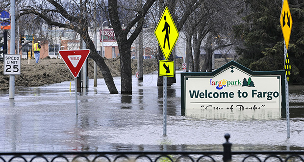 In this April 8, 2011, photo, a welcome sign for Fargo, N.D., sits in the rising floodwaters of the Red River as a flood engineer for the U.S. Army Corps of Engineers, at left, inspects the levee protecting the downtown area. (AP file photo)