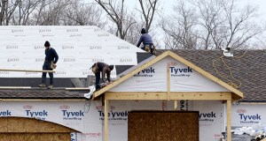 In this March 21 file photo, roofers work on a new home in Pepper Pike, Ohio. U.S home construction rose moderately in March, the Commerce Department said Wednesday. (AP file photo)