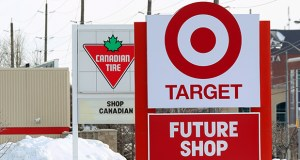 In this March 4, 2013, photo, a Canadian Tire sign gives a cold shoulder to a new Target store in Guelph, Ontario. Canadians, who for years had shopped at Target just over the border in the U.S., have been disappointed that prices at the new stores are higher. (AP file photo: The Canadian Press)