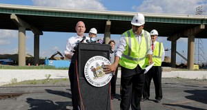 Delaware Transportation Secretary Shailen Bhatt, right, tries to affix a state seal that fell off a lectern as Delaware Gov. Jack Markell, left, speaks at a news conference Thursday in front of the Interstate 495 bridge over the Christina River near Wilmington, Del. (AP photo)