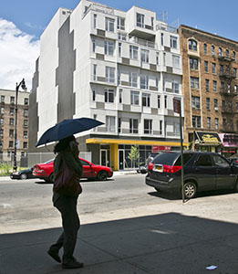 A seven-story modular apartment building called the Stack, left, is shown next to a decades-old residence in the Innwood neighborhood of New York. (AP photo: Bebeto Matthews)