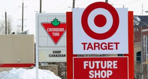 In this March 4, 2013, photo, snow is piled in the parking lot of the new Target store in Guelph, Ontario, as Canadian Tire posts a Canadian message on its sign. (AP Photo/The Canadian Press)