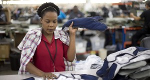 In this Sept. 19 photo, Laurette Eugene makes the final assembly of body armor at the Point Blank Body Armor factory in Pompano Beach, Florida. As the third quarter nears an end, economists envision a strengthening economy through the end of 2014 and into 2015. (AP photo)