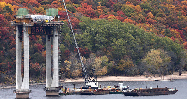 Working from barges in the St. Croix River, workers continued construction this week at one of five river pier locations for the new $626 million St. Croix Crossing. Stunning fall colors on the river bluffs provided a background for the construction. (Staff Photo: Bill Klotz)